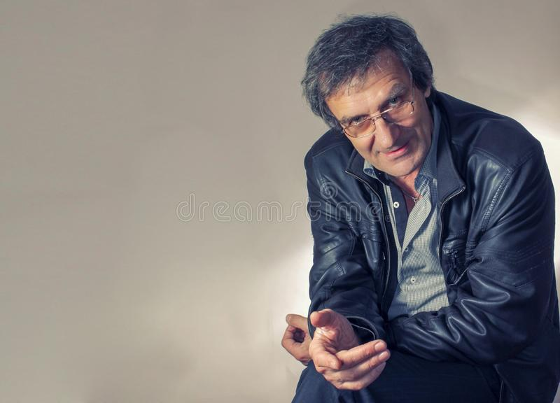 Portrait of an adult gray-haired man in glasses sitting with a questioning look on a chair in a light gray shirt and royalty free stock photography