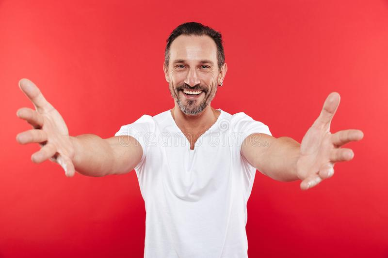 Adult happy man want to hug you. Portrait of an adult happy man standing isolated over red background want to hug you stock photos