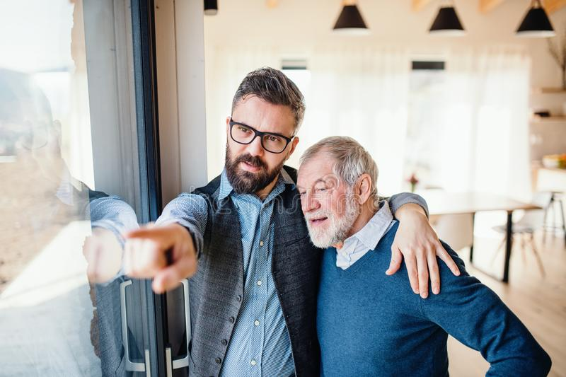 A portrait of adult hipster son and senior father indoors at home, talking. royalty free stock image
