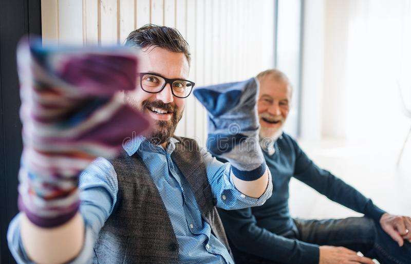 Portrait of adult hipster son and senior father sitting on floor indoors at home, having fun. stock photos
