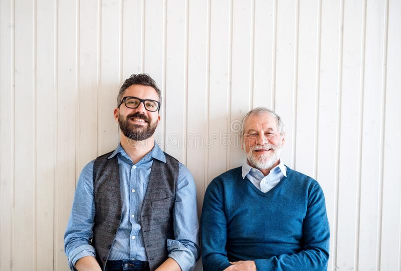 A portrait of adult hipster son and senior father sitting on floor indoors at home. royalty free stock photography
