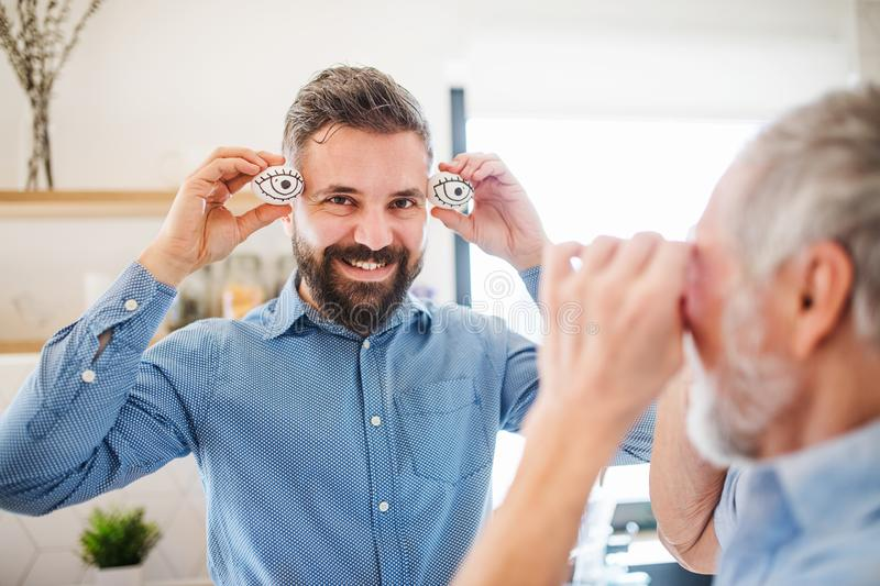 A portrait of adult hipster son and senior father indoors at home, having fun. royalty free stock photo