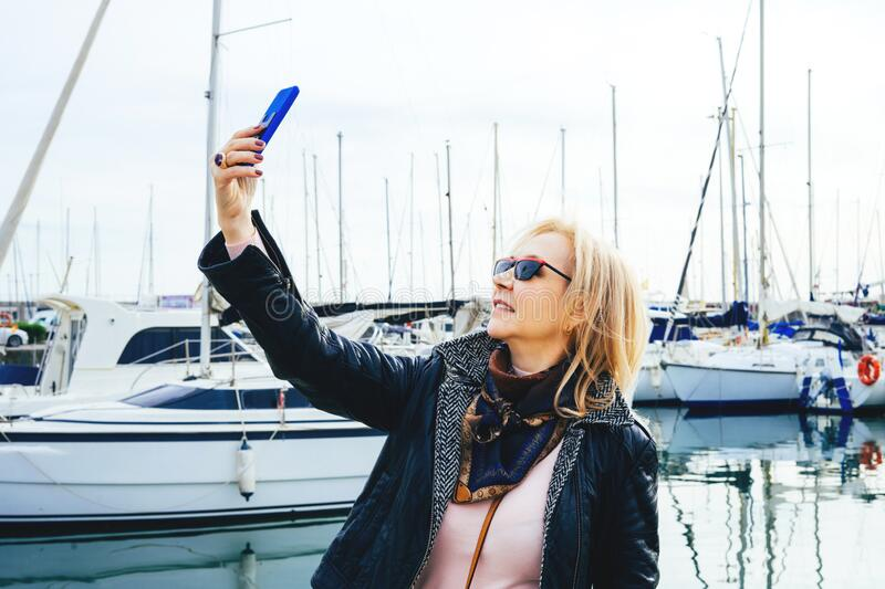 Portrait of an adult lady in sunglasses standing in a marina on yachts background and makes selfie on smartphone. Portrait of an adult beautiful lady in a royalty free stock image