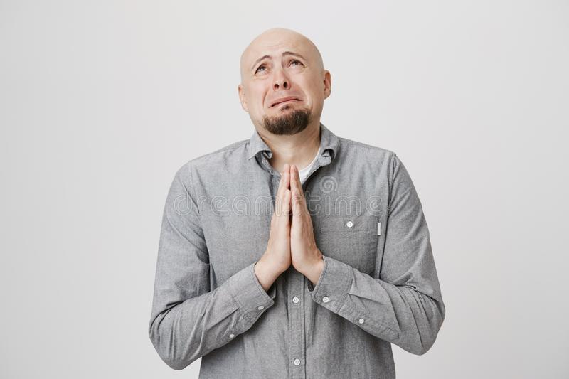 Portrait of adult male looking sad and miserable holding his hands in pray over white background. Poor man in casual stock photography