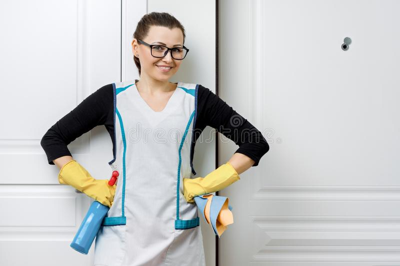 Portrait of adult positive smiling woman in glasses and apron for cleaning rubber gloves with detergents, white door background, royalty free stock images