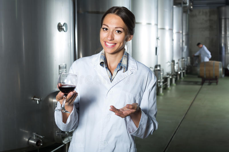 Portrait of adult woman looking at wine sample. Portrait of adult women in uniform looking at wine sample in glass on winery manufactory royalty free stock photos