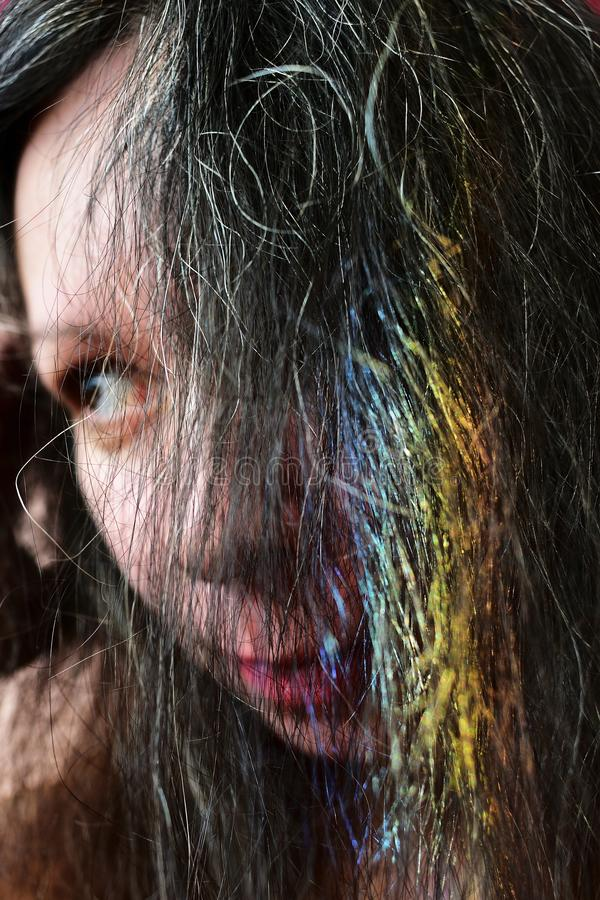 Portrait af a young woman with a rainbow on dark hair stock photo