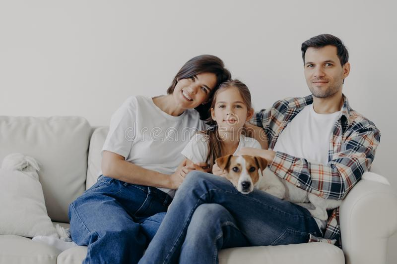 Portrait of affectionate family cuddle and sit together at couch in living room, change their home, have happy expressions. Father royalty free stock images