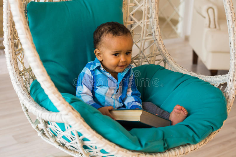 Portrait of African American baby boy holding book on sofa stock photography