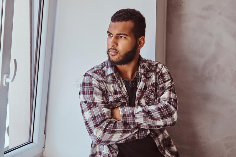 African-American bearded man wearing a checkered shirt with his arms crossed sitting on a window sill. Portrait of an African-American bearded man wearing a royalty free stock photos