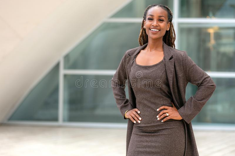 Modern portrait of African American female business person standing by office building, architecture firm, law, finance or other p. Portrait of an african stock images