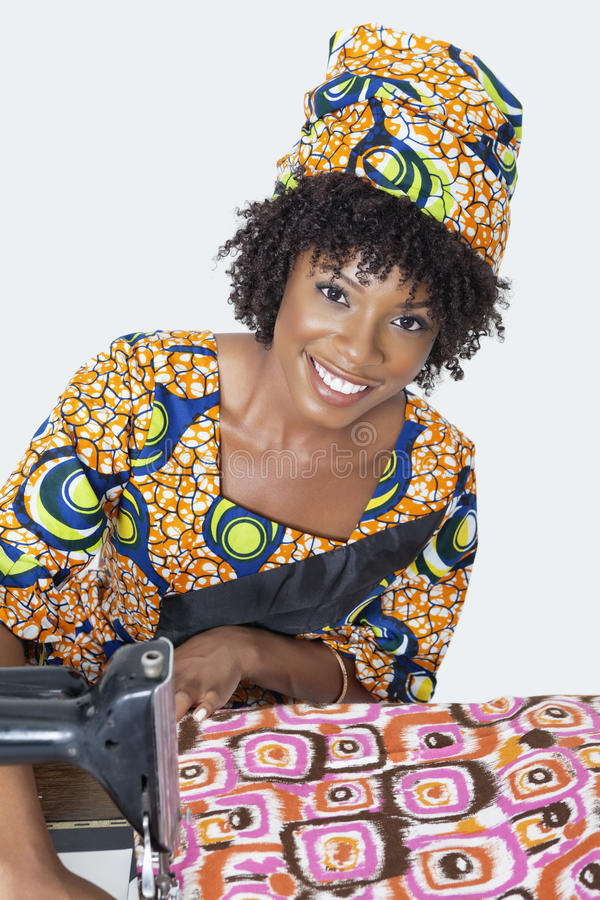 Portrait of an African American female fashion designer sewing fabric over gray background royalty free stock image