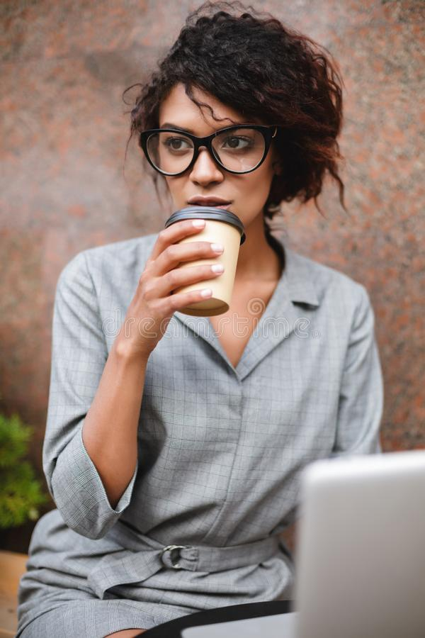 African American girl in glasses sitting on bench and drinking coffee while dreamily looking aside. Young lady with dark. Portrait of African American girl in royalty free stock photography