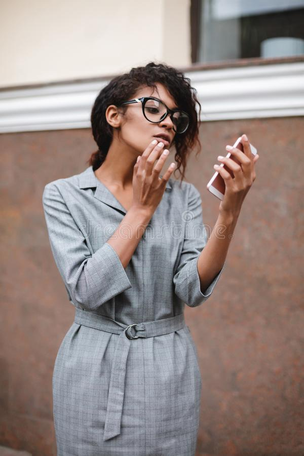 African American girl in glasses standing with cellphone in hand. Young beautiful lady with dark curly hair in gray. Portrait of African American girl in glasses royalty free stock photo