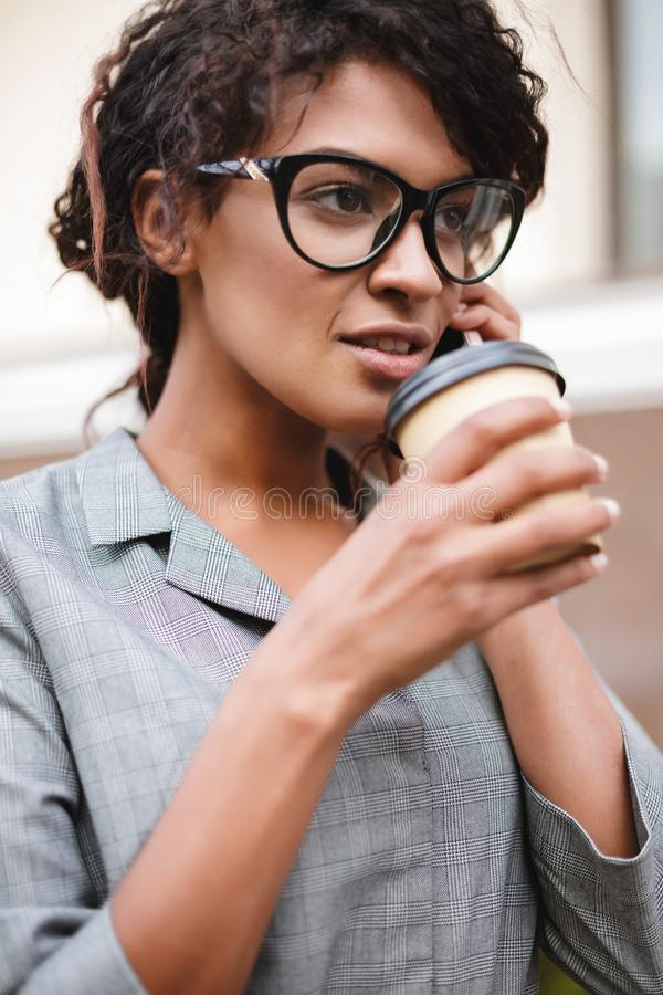 African American girl in glasses standing and talking on her cellphone with coffee in hands. Thoughtful lady with dark. Portrait of African American girl in stock photo