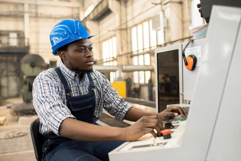 Portrait of African American Machine Operator. Portrait shot of highly professional worker wearing checked shirt and overall operating machine at production stock photos