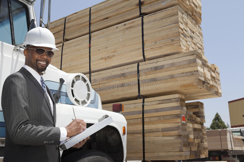 Portrait of African American male contractor writing notes while standing by logging truck royalty free stock images