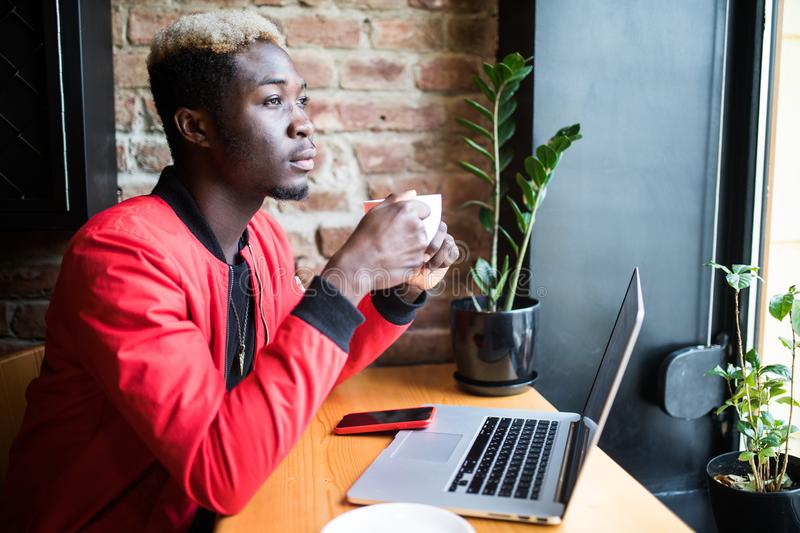 Portrait of an African American man in a jacket drink coffee and work on a laptop royalty free stock images