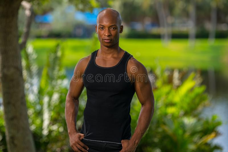 Portrait of a African American man posing outdoors in a tank top shirt royalty free stock images