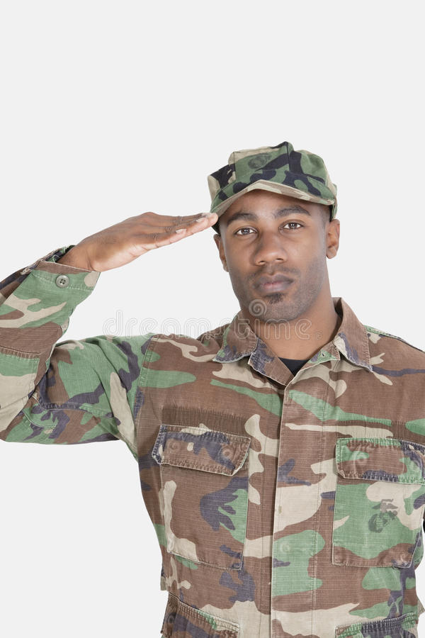 Portrait of an African American US Marine Corps soldier saluting over gray background royalty free stock images