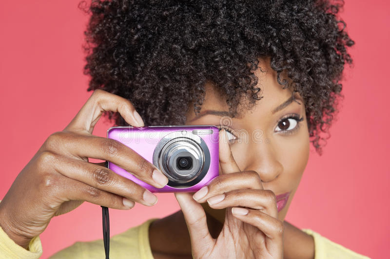 Portrait of an African American woman taking picture from camera over colored background stock photo
