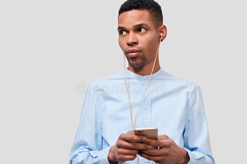 African American young man holds modern smart phone, blogging on cellphone. Handsome male listening the music on earphones stock photo