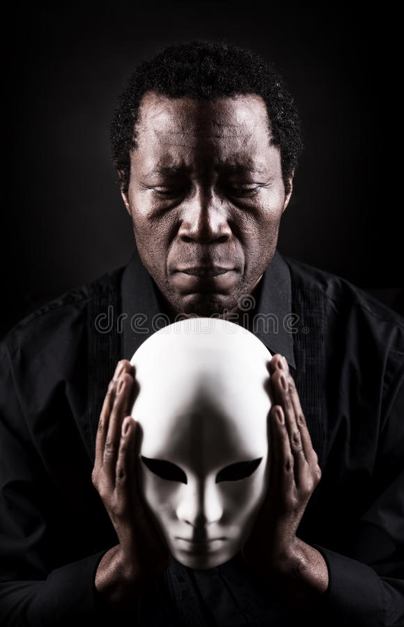 Portrait of african black man with white mask. Dramatic art portrait of african black man with white mask royalty free stock photography