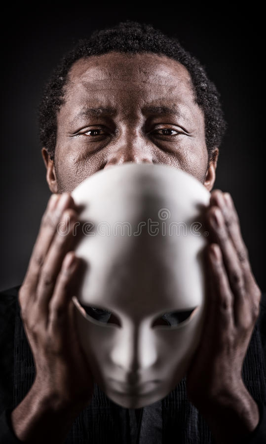 Portrait of african black man with white mask. Dramatic art portrait of african black man with white mask stock photos