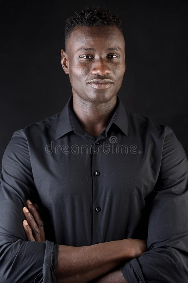 Portrait of a african man arms crossed on black background royalty free stock photography
