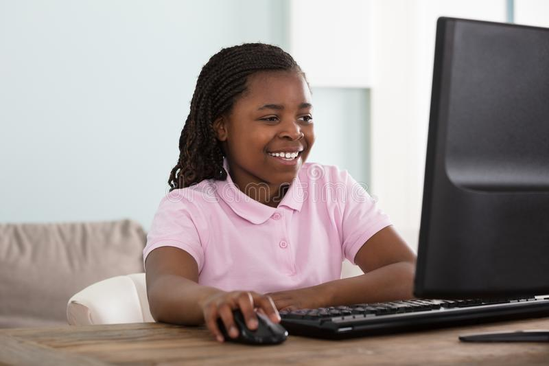 Smiling Girl Using Computer stock photo