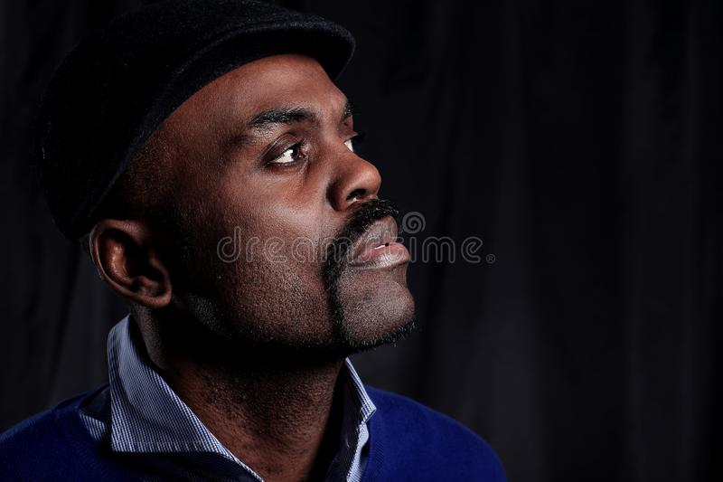 Black business man overturned hat, black background. Portrait of an African wearing fashionable caps stock photo