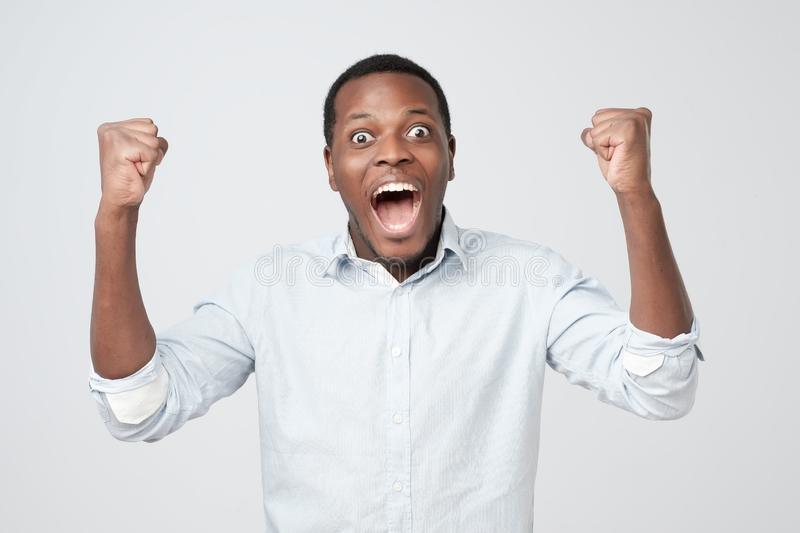 Portrait of african young handsome man surprised with news he got. royalty free stock images