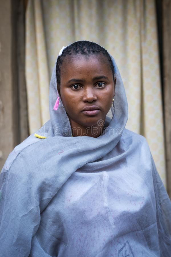 Portrait of an African young woman wearing a hijab in a slum of the city of Bissau, in Guinea-Bissau. Bissau, Republic of Guinea-Bissau - January 29, 2018 stock photography