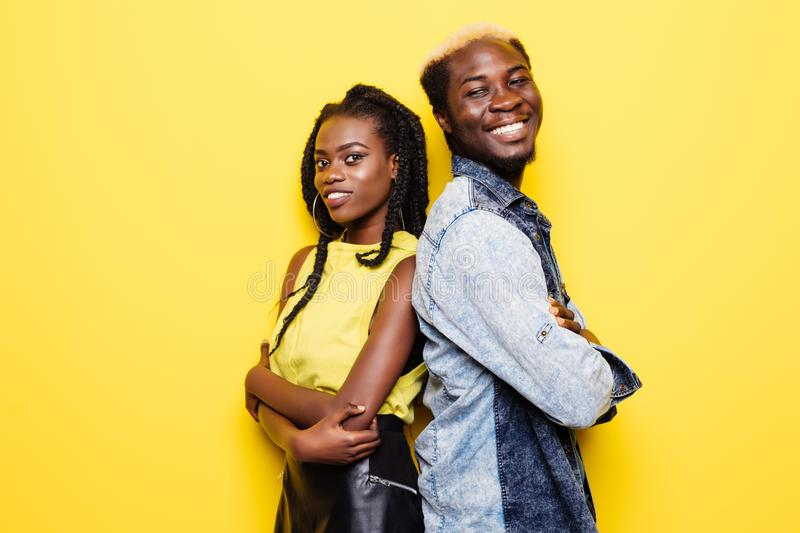 Portrait of afro american couple standing back to back isolated over yellow background stock photos