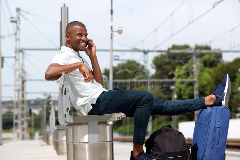 Male traveler at railway station using cellphone. Portrait of afro american traveler sitting with luggage and talking on cellphone at train station royalty free stock photo
