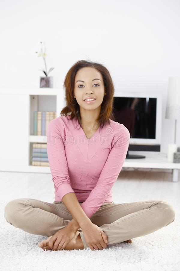 Portrait of afro woman at home. Sitting on living room floor, smiling royalty free stock photo