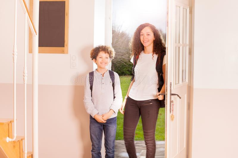 Happy boy and girl coming back home from school. Portrait of age-diverse children, smiling boy and girl with backpacks, coming back home from school royalty free stock photos