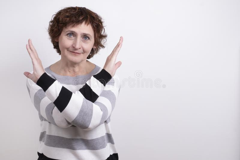 Portrait of an age woman gesture, crossed in front of him refuses to communicate. Lady brunette , emotional stop, the front of a white wall, place the text stock photo