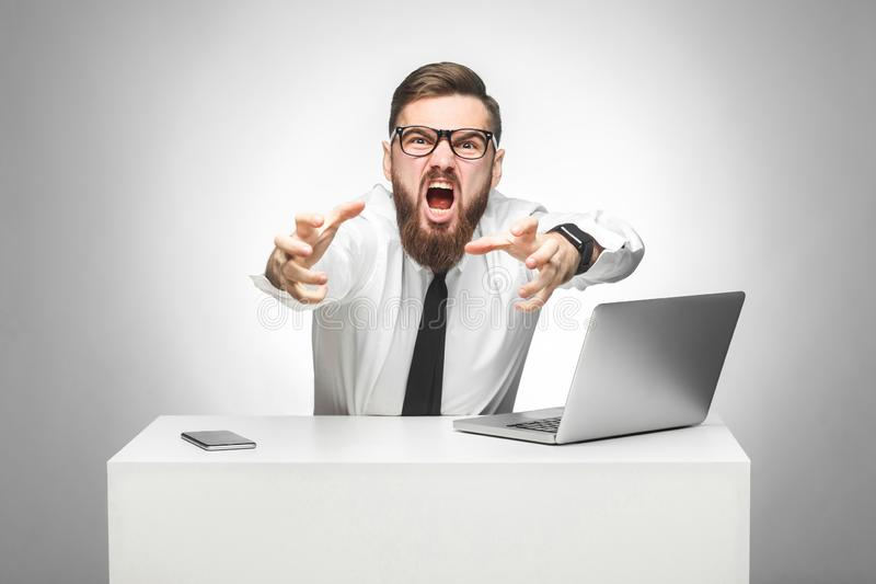 Portrait of aggressive angry young businessman in white shirt and black tie are blaming you in office and having bad mood, stock photo