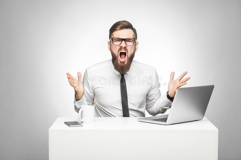 Portrait of aggressive businessman in white shirt and black tie are sitting in office and having bad mood with raised arms looking royalty free stock images