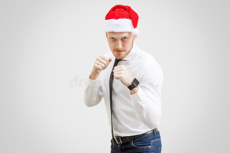 Portrait of aggressive handsome businessman in white shirt, black tie and red new year hat, looking at camera with boxing fist stock photo
