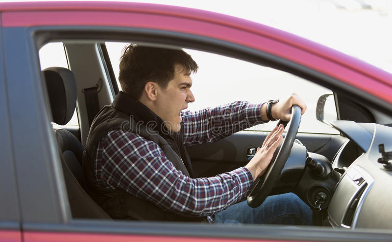 Portrait of aggressive male driver honking in traffic jam. Closeup portrait of aggressive male driver honking in traffic jam royalty free stock photography