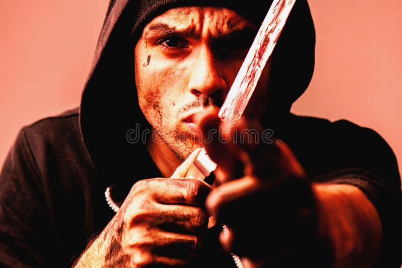Portrait of aggressive robber with knife stylized in red light stock photos