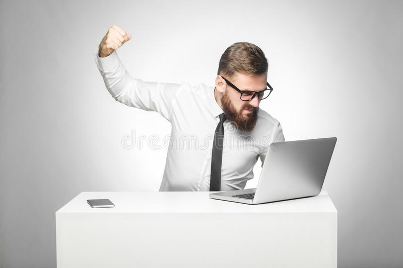 Portrait of aggressive unhappy businessman sitting in office and having bad mood are ready to punch a worker through a webcam with. Fist and angry face. indoor stock images