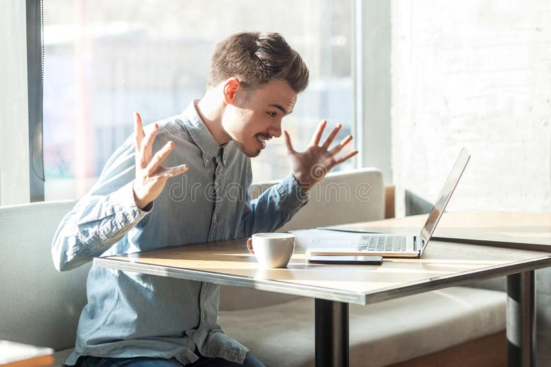 Portrait of aggressive unhappy young businessman in blue shirt are sitting in cafe and having bad mood. Are admonishing a worker through a webcam with raised stock images
