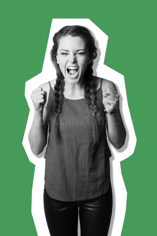 Portrait of aggressive young woman on color background royalty free stock images