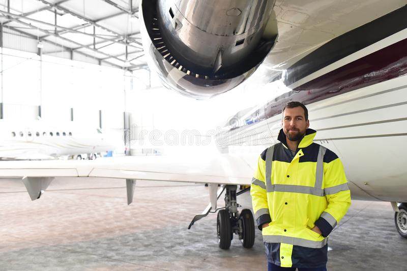 Portrait of an aircraft mechanic in a hangar with jets at the airport - Checking the aircraft for safety and technical function. Closeup photo royalty free stock photos
