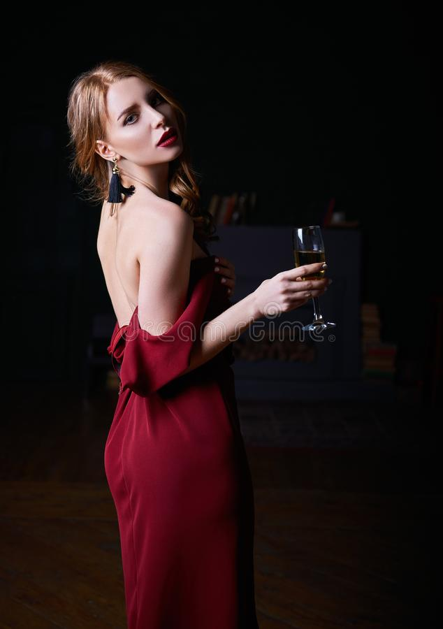 Portrait of alluring beautiful young woman in lowered red dress with a wineglass of champagne in hand royalty free stock images