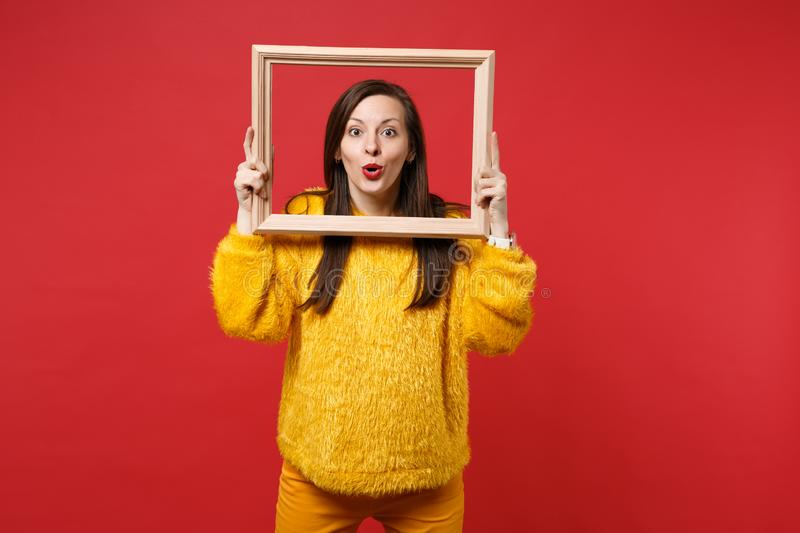 Portrait of amazed attractive young woman in yellow fur sweater holding picture frame isolated on bright red wall stock photo