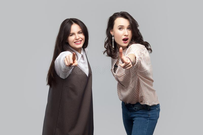 Portrait of amazed beautiful brunette girls in casual style standing, pointing and looking at camera with surprised face royalty free stock images